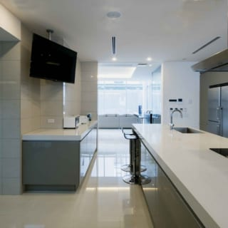 ドイツ・ポーゲンポール社の高級キッチンを入れた1階キッチン。正面に進むとバーカウンター、その先にはリビングが広がる。ホームパーティーの際はこのキッチンにプロのシェフが出張し、おもてなし空間の1つになることも