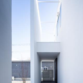 建物の壁の隙間は、玄関ポーチと自転車置き場に。上部の窓には陽光や風が入る構造