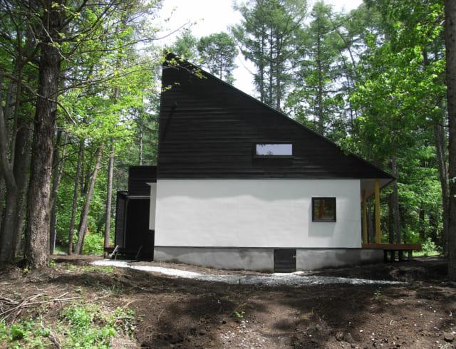 木立の中に佇むOさんの別荘。左官仕上げの白壁と黒杉板のコントラストが美しい