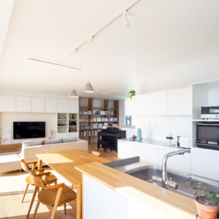 リビングの壁面には、大容量の収納と本棚。冷蔵庫脇には約2帖パントリーも。料理をしながら景色も楽しめる