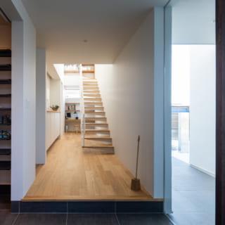玄関の隣には、大容量のシューズクローゼット。階段を吹き抜けとしたことで、上部からの光が1階まで下りてくる