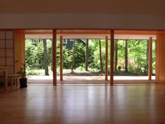 構造を支える柱と庭にそびえる木の幹がと同化。室内外が一体化したような感覚になる