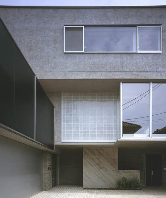 エントランスは正面が賃貸世帯、左が施主さま世帯。広い間口とL字のアクセント壁が2世帯を緩やかに仕切る