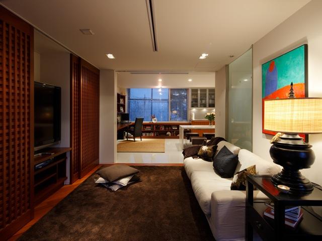 2階ファミリーリビング。写真左のテレビスペースは、必要に応じて3枚の格子戸で隠せるようになっている。奥のダイニングキッチンとひと続きなので家族の居場所の一体感が高いうえ、キッチンの窓越しの豊かな緑も見える