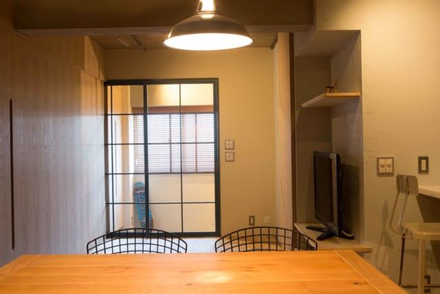 リビングから土間を見る。もともと洋室にあった窓と、室内へ入る扉を開けると、反対側の窓まで一直線につながり換気能力が高まった。写真左側はすべて収納。引き戸に余計な装飾をつけず、素材感を生かしたシンプルなつくりにした。そこが収納だと気が付かないお客様も多いのだとか