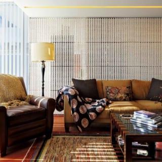 シノワズリ家具が映える来客用リビング。床は明るい赤みが特徴のアフリカ産チーク材。ソファ背面の壁は、立体タイルをレースのように透かし積みにした贅沢なもの。ゲストとの歓談の場に上品な華やぎが生まれるとともに、壁向こうの廊下を行き来する人とのほどよい一体感も創出