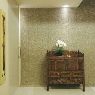 1階エントランスから2階へ向かう階段の上り口には、チベットの希少なアンティーク家具が置かれている。白大理石の床、外壁と同じざらついた質感のコンクリート壁など、シンプルで高級感のある内装が、個性的な骨董家具をしっかり受け止めている