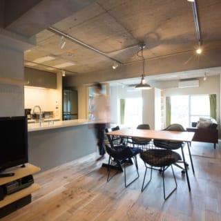 広々としたワンルームに生まれ変わった室内。換気も十分、窓の上に設置されたエアコンの空気が隅々まで届き快適に暮らせるようになった。フリースペースと寝室スペースを仕切る収納は可動式。天井に複数通る梁の下に収まるようになっており、状況に応じて空間を分けられる