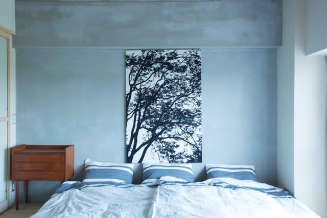 部屋の奥に位置する寝室スペース。マットレスを置き、昼間は重ねてしまえば隣接するフリースペースと一続きの広々とした空間に。モルタルの壁面がシンプルさを際立てている