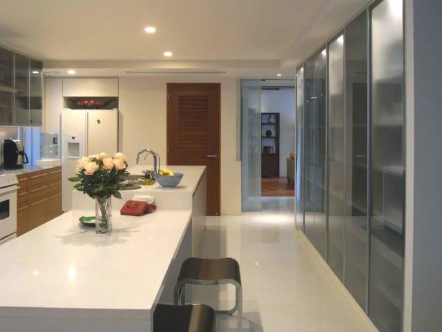 2階ダイニングキッチンから来客用リビングを見る。右奥の出口からすぐに来客用リビングへ行くことができ、ゲストをもてなす際も料理を運びやすい。中央奥の木製ドアの先はランドリールームで、家事動線がとてもよい