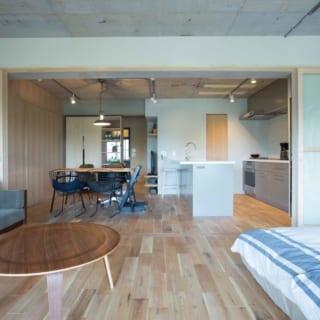 キッチン奥の木製の引き戸から浴室やトイレにつながる。キッチンはペニンシュラ型。一般的にコンロとずらして配置するシンクも端に寄せ、十分な調理スペースを確保した。手前はフレキシブルな空間。マットレスを重ねて片付ければフリースペースが広がり、より贅沢な使い方ができる