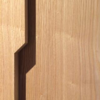 壁面の収納扉には取手を付けない代わりに、手をかけるスリットをいれた。扉が重なるとできる影まで美しい