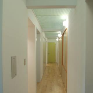 白ベースのシンプルモダンでまとめられた、箱型の水回りと収納スペース。廊下の天井はFRPのグレーチングで上部からの光が差し込み空気も循環する
