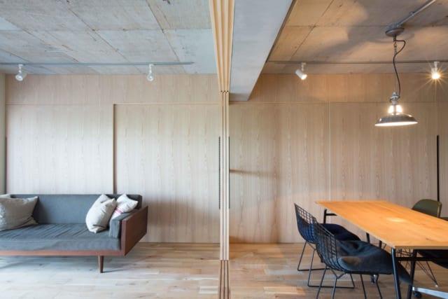 リビングダイニングとフリースペースを仕切るのはガラスが入った引き戸。おおらかに空間を区切り、家のどこにいても外の景色が楽しめる。壁面はすべて収納。取手を付けない代わりにスリットが入っている。天井現しのコンクリートも、空間のシンプルな構造を際立たせている