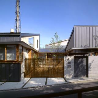 洗足流れの遊歩道からみたKさん邸。中央のウッドデッキと収納スペースで左右のKさん邸とお母様邸がつながる。木製の竪格子が視線を遮りつつ風通しを実現
