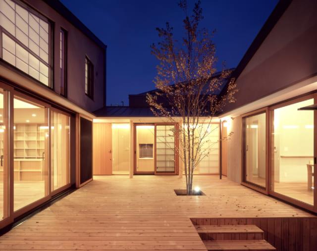 夜のウッドデッキ。建物から溢れる光と桂の木に設置された灯りに照らされ、能舞台のような雰囲気に