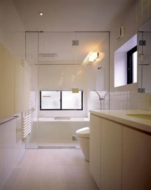 バスルーム、洗面、トイレはガラスで仕切られた一体型。バータイプのタオル乾燥機もホテルを思わせる