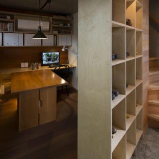1階の玄関(土間)と事務所スペース。格子状のオープンシェルフは、本棚と靴棚と間仕切りを兼ねる