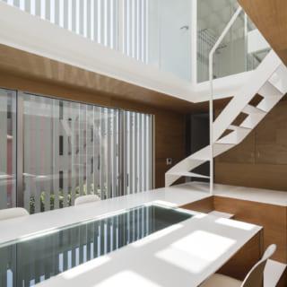 3階サブリビング。コンパクトだが南に大きな窓があり、造作テーブルの上部が吹抜けなので開放感は申し分ない。造作テーブルは、一部を4階への階段にしてスペースを有効活用。階段は途中からオープンなデザインに変わり、オブジェのような存在感で空間のアクセントになっている