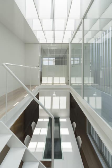 4階への階段からの眺め。格子を入れたトップライトやガラスが純白の内装に映え、モダンな空間に仕上がった