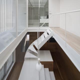 3階~4階の吹抜け。4階のトップライトから入る光が、3階の造作テーブルのガラスを通して2階まで届く