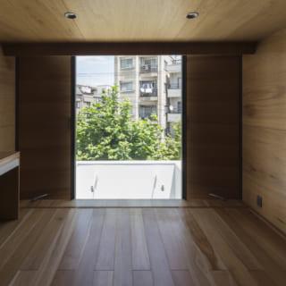 3階子ども室。道路側に窓があるので街路樹の緑の先に抜け感のある景色が見え、居心地がいい。中央の窓はFIXだが、両脇の壁のように見えるところは、少しだけ開く通風用のドア。このドアは、外側は外壁と同素材、内側は室内の壁と合わせてあり、デザインに馴染んでいる