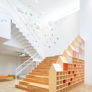 【1階/子どもゾーン】2階への階段はオープンなひな壇状。側面はシューズロッカーになっている