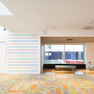 【1階/子どもゾーン】子どもゾーンのエントランスホールは、子どもが喜びそうな明るくポップな空間。写真中央のガラス越しにはメインプールがあり、親御さんはここで子どもたちのスイミングを見学できる