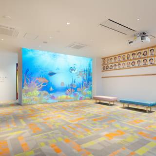 【1階/子どもゾーン】エントランスホールの大画面プロジェクター。魚が泳ぐ様子など知育にも役立つ映像を流しており、子どもたちも興味津々