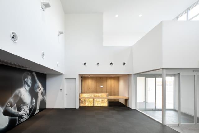 【1階/大人ゾーン】大人専用エントランスとレセプション。開放的な吹抜け空間はシックなモノトーン調でまとめられ、大人が落ち着けるモダンなホテルのような雰囲気