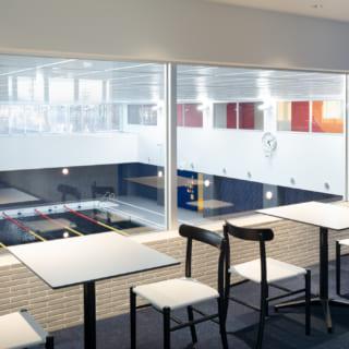 【2階/大人ゾーン】2階の大人ゾーンの一角には、1階メインプールの吹抜けに面した飲食スペースがあり、カフェ風の空間からプールの様子を眺めることができる