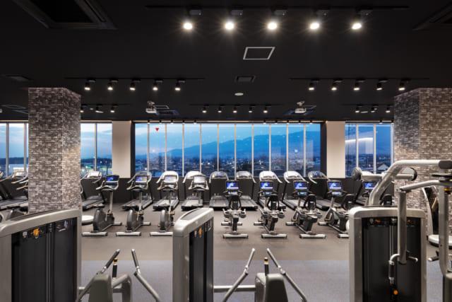 【3階/大人ゾーン】男女共用のジムスペース。浅間山の全景を望む連続窓に向かって各種マシンが配置されており、雄大な景色を眺めながらトレーニング可能。このエリアならではの贅沢なロケーションを活かした空間が、利用者に喜ばれている