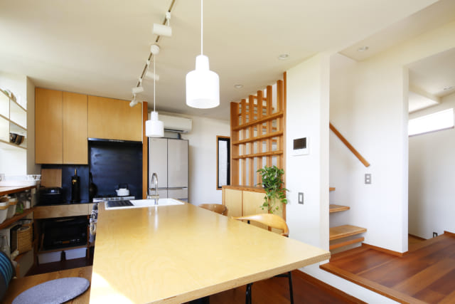 コンパクトで使いやすいキッチンと、シンクと一体となったテーブルが特徴。白い壁は、卵の殻を利用した素材で吸放湿抜群