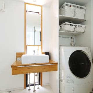洗面に窓をあしらい、自然光を取り入れる工夫も。鏡の裏はガラス棚の収納を設置