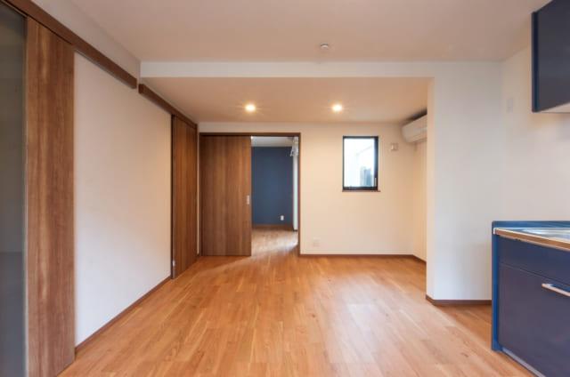 1階賃貸A住戸、LDKから寝室までを見る。一続きになった空間は道路側にリビング、奥に寝室を配置し、騒音も考慮した。道路側にある窓に加えて、写真正面の窓からもテラスを通して光が入るためLDKはいつでも明るい。寝室からはテラスに出ることもできる