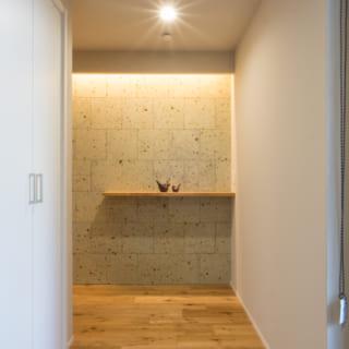 1階、自宅の玄関から階段につづくホールを見る。正面には以前の自宅の塀に使われていたものと同じ素材、大谷石を貼った。「昔の自宅からのものを、雰囲気や仕上げで残せたらいいとS様と話していました」と平井さん。子ども部屋にはお嬢様からのご要望で柱を移植したという