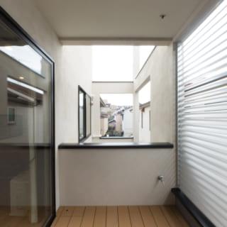 2階、自宅LDKにつづくバルコニーは、アルミ製の稼働ルーバーのおかげで隣家の気配を感じることなく光と風を室内まで通すことができる。バルコニーの奥は吹き抜け。隣り合うことで視線が抜けバルコニーがさらに広く感じる