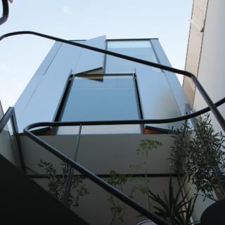 3階、4階の外観を見上げる。3階、4階は外の景色を眺めるFIX窓の脇に、少しだけ開く通風用のドアを設置。ドアの外側は外壁と同じ素材なので、一見すると壁のように見え、とてもスマート。このドアを開くと、モダンな外観がよりいっそう洒落た印象になる