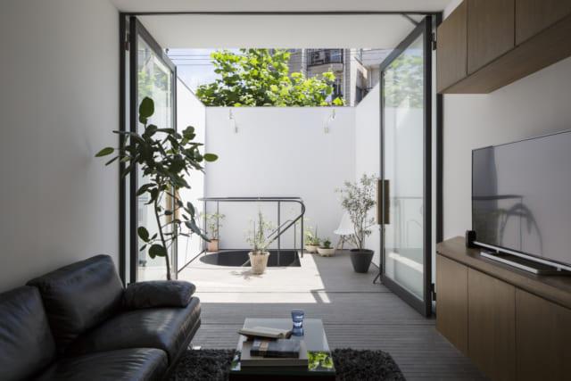 2階LDKからテラスを見る。テラスは街路樹の緑が見える高さの白壁で囲われ、プライベート感たっぷり。テラスとLDKの床は同じレンガタイルなので地続き感がアップ。両開きのガラス扉を全開放すると、どこまでが屋内でどこからが屋外かわからなくなるほど開放的だ