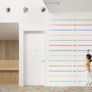 【1階/子どもゾーン】レセプション脇の壁には高さを示すラインを入れた。ジャンプ力を簡単にチェックできるため、喜んでチャレンジする子どもが続出