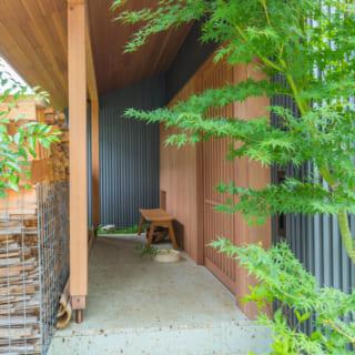 モミジが出迎えてくれる玄関。キレイに並べられた薪棚は、玄関と道路を緩やかに仕切る衝立となっている