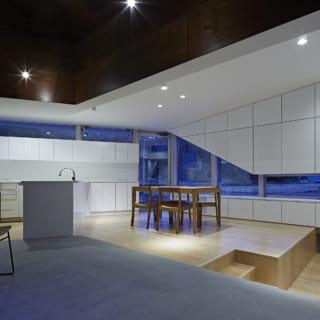 キッチンは外から見えないよう、東側の壁面のうらに配置した。リビングまで続く窓の上下は、すべて収納棚として使用できる。手前、ダークな色合いでまとめた軸空間はLDKなどがある周りの空間よりも天井が高いため、裸電球を垂らしている