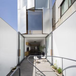らせん階段から2階に上がると、白壁に囲まれたレンガタイルのテラスがお出迎え。ここはテラスであると同時に住居へのエントランスでもあり、両開きのガラス扉から邸内に入っていく。玄関をつくらなかった分、スペースを有効活用でき、奥のLDKもゆったりとした広さになった