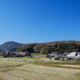 岡山県の田園風景に佇むKさん邸。遠景からは、屋根に穴があいたような独特のフォルムが存在感を発揮