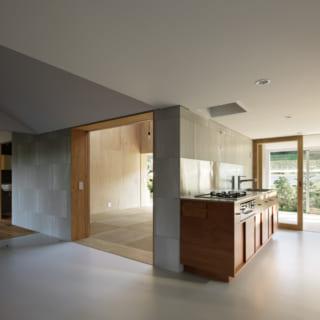 中央のリビングを取り囲むように、ダイニングキッチンや寝室、水回りを配置。キッチンと板間は、窓を開くと一続きの大空間に