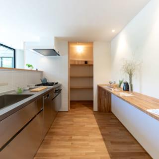 キッチンから食品庫を見る。キッチントップの立ち上がり部分に手元灯を設けキッチン全体を過不足なく照らす