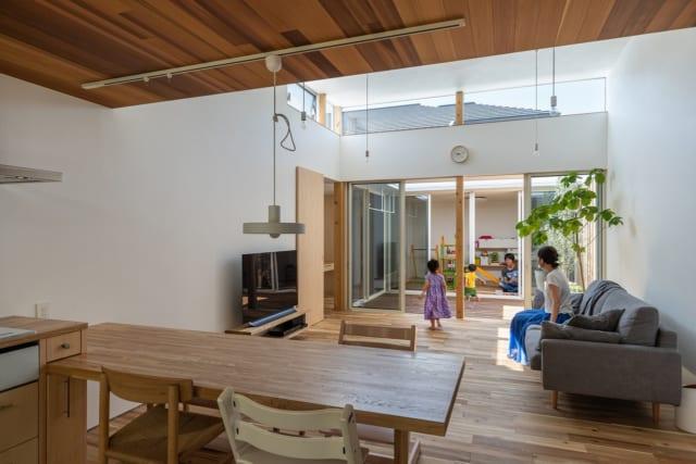 ダイニングから見たリビング。大きな窓の向こうに繋がるウッドデッキや子ども部屋の様子が見通せる。上部の窓から差し込む光が、LDK全体を明るく照らしてくれる