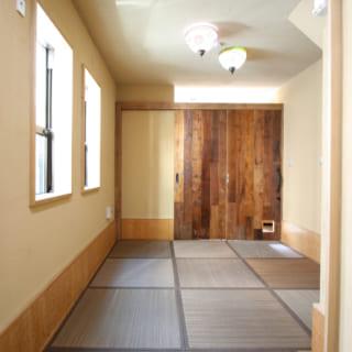 親世帯の和室はカラーリングされた畳で温かな雰囲気に。奥の引き戸を開けると、共用土間とひと続きになる