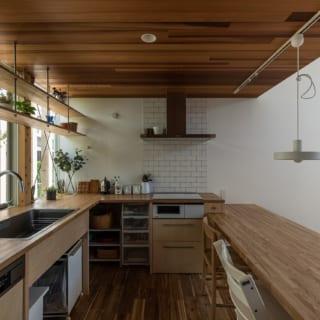 木目が生かされたキッチン、ダイニングテーブル、キッチン収納棚はすべて造作。天井板には風合いあるレッドシダーを採用している