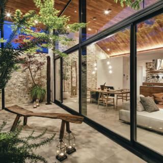 テラスからLDKを見る。ガラスで仕切られただけなので、テラスにいても邸内の家族との一体感が高い。塀で囲われ、空と緑以外の余計なものが目に入らないテラスはリゾート感にあふれ、ここが東京であることを忘れてしまう